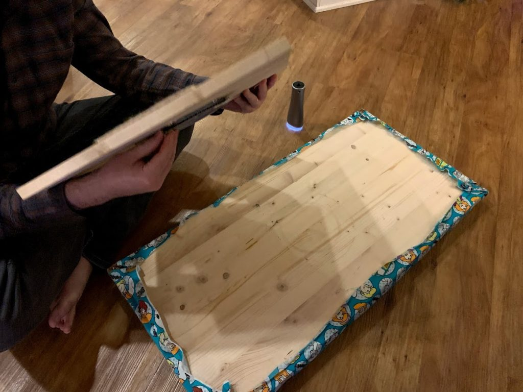 Long board flipped upside-down, preparing to attach base board for making therapy spinning board for kids.